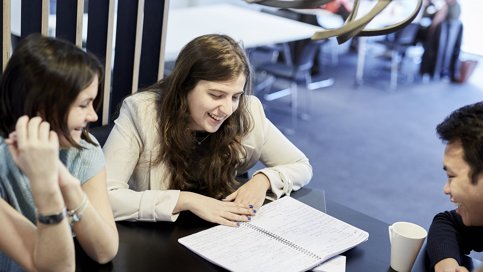 Postgraduate university students work in communal study area at GradPad London